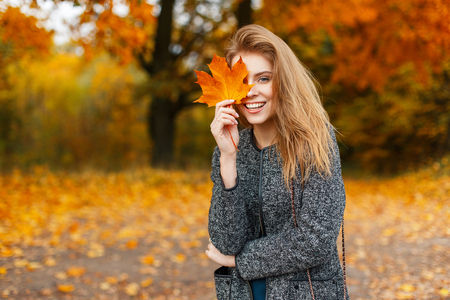 Happy young beautiful woman with a smile holds an autumn yellow leaf in the autumn day in the park