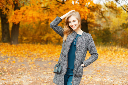 Beautiful stylish young woman with a smile in autumn clothes near trees with yellow foliage Stock Photo