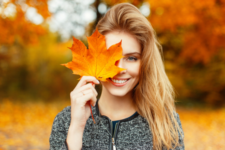 Beautiful happy woman with a smile holds an autumn yellow leaf near the face