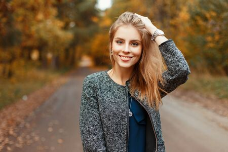 Happy beautiful woman with a smile in an autumn stylish coat posing in the park