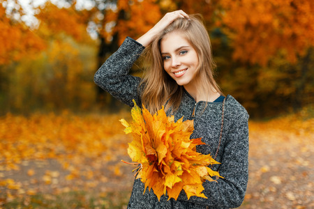 Happy beautiful woman with a smile with autumn yellow flowers in the park Stock Photo