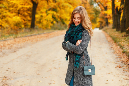 Happy beautiful young woman with a smile in stylish clothes with a scarf posing in an autumn yellow park