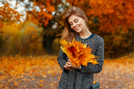 Happy beautiful woman with autumn yellow leaves in the amazing color park
