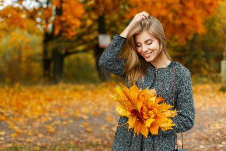 Beautiful young woman with a cheerful mood with autumn yellow leaves