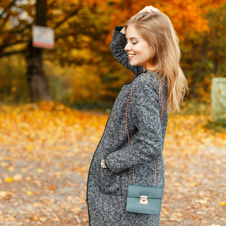Beautiful stylish girl in a trendy coat in an autumn park