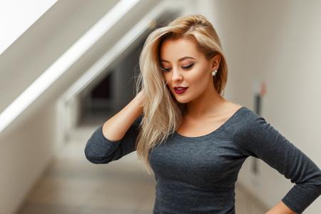 Heureuse belle jeune fille en robe grise à l'intérieur