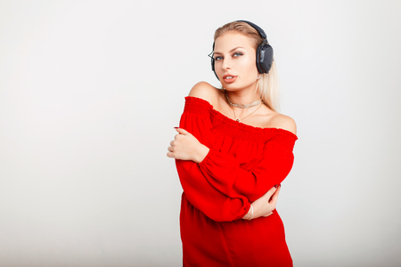 Portrait of a beautiful young DJ girl with headphones in a red dress listening to music on a gray background Stock Photo