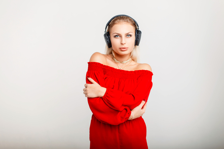 Fashionable beautiful girl in a stylish red dress with headphones listening to music on a gray background