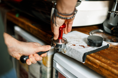 Barista presses ground coffee using tamper Stock Photo