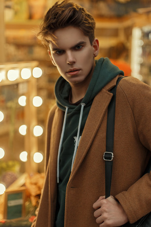 Fashionable young man with a haircut in a vintage fashion coat with a bag near the store with light bulbs