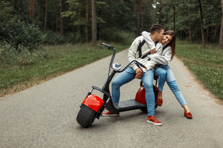 Young stylish beautiful couple in fashionable brand clothes near red electric bike