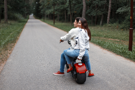 Beautiful couple riding an electric bike in a forest on the road Stok Fotoğraf
