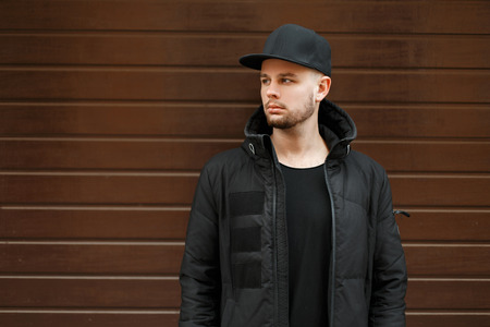 01cf7ad73de  90925927 - handsome young hipster man in a black stylish baseball cap and winter  jacket stands near the wall