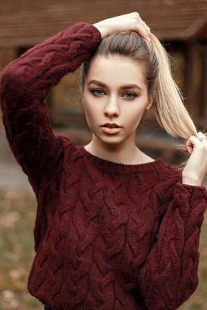 Natural portrait of a beautiful young woman in a vintage knitted sweater outdoors Archivio Fotografico