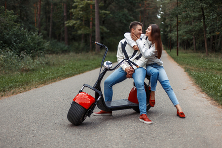 Beautiful fashionable couple in stylish denim clothes and red shoes with an electric scooter in a park on the road