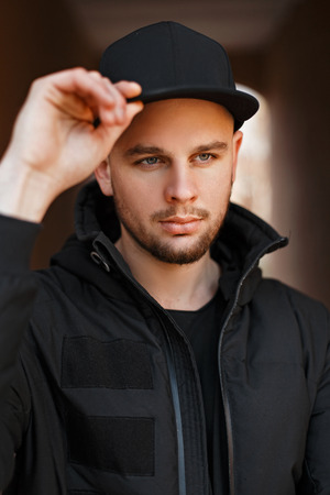 9433e3deda5  90927178 - Street portrait of a handsome young man in a black stylish  baseball cap and winter jacket