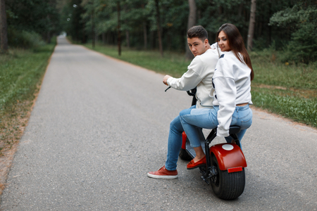 beautiful young couple in blue jeans and white sweaters ride an electronic bike