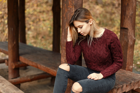 Beautiful young woman in a stylish knitted sweater sits on a wooden bench in nature