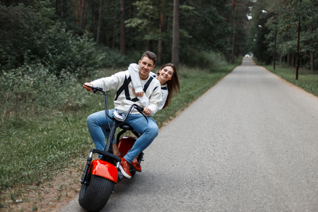 Couple in love riding an electric bike on the road