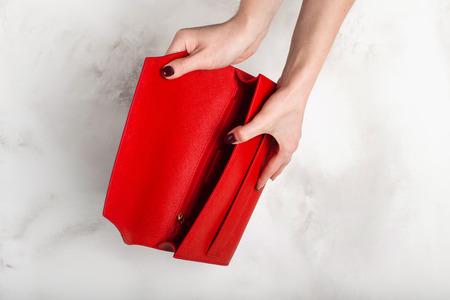 Fashionable red female handbag on a white granite texture