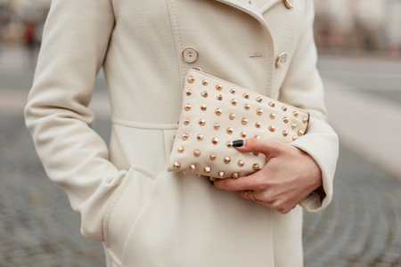 Fashionable stylish womens handbag in womens hands on the street Stock Photo