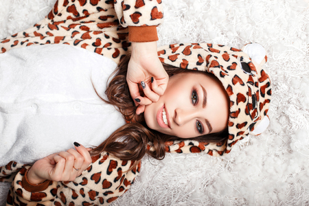Beautiful happy young woman with a smile in a funny bear pajamas