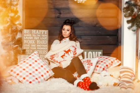 Stylish young beautiful woman in a trendy knitted sweater with red Christmas socks and on a bed with festive lights