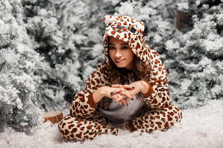 Beautiful young woman in funny pajamas sitting near a Christmas tree with snow