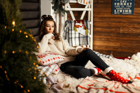 Fashionable beautiful young woman in a knitted vintage sweater with red Christmas socks lies on the bed