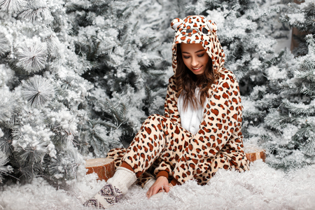 Funny young happy woman in fashionable bear wearing pajamas with hood sitting near Christmas trees with snow in studio Stock fotó