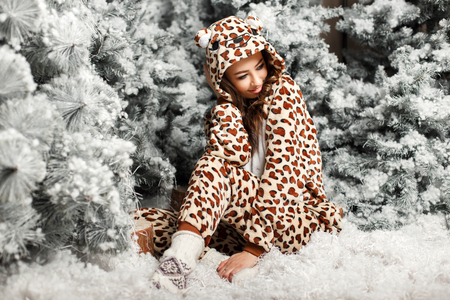 Happy cute girl in a trendy bear pajamas sitting near a Christmas tree Reklamní fotografie