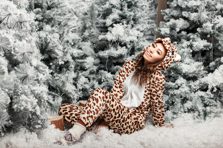 Funny happy beautiful woman with a smile in a trendy bear pajamas near a Christmas tree with snow in the studio Stock fotó