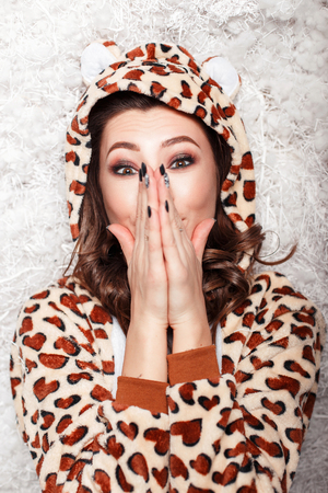 Beautiful young woman in a fashionable funny pajamas with a hood shows an incredible emotion.