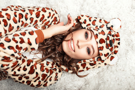 Happy beautiful woman with a smile in funny pajamas with a hood on the floor. Frame from the top. Stock fotó