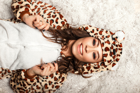 Happy young woman with a smile with teeth in a funny bear pajamas with a hood, indoors Stock fotó
