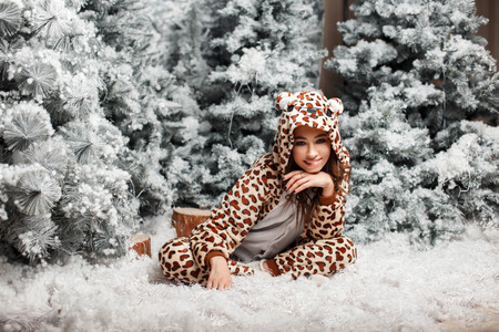Funny happy woman in a trendy bear pajamas sitting near a Christmas tree with snow in the studio