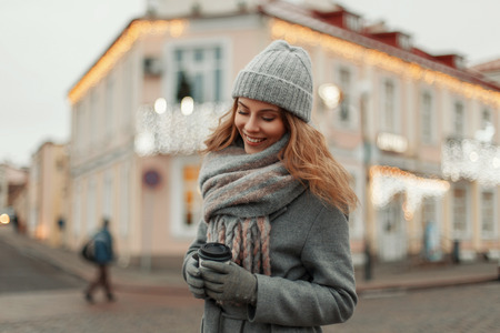 Happy beautiful girl in a fashion vintage coat with a knitted stylish hat and scarf with a glass of coffee walking in the city on a winter day Stock Photo