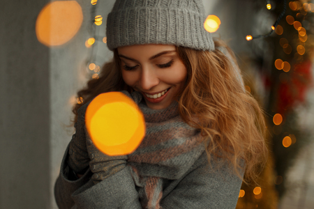 Beautiful happy young girl with a smile in knitwear clothes in a fashion coat with a stylish knitted hat with scarf on a holidays on a background of lights 免版税图像