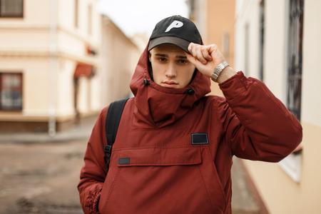 배낭과 빨간 세련 된 재킷에 유행 젊은이 도시의 거리에서 야구 모자를 조정 스톡 콘텐츠 - 96658176