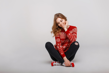 Funny beautiful girl in a fashion red winter sweater with Christmas socks sitting on the floor Stock Photo