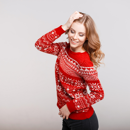 Funny beautiful happy woman with a smile in a trendy red sweater on a gray background Stock Photo