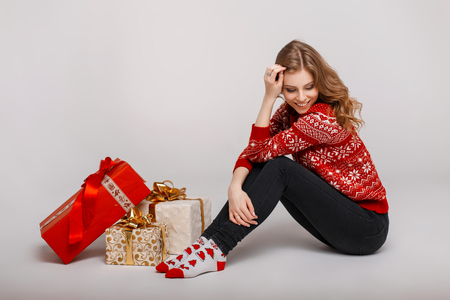 Beautiful young happy woman in a vintage sweater sits near gifts on a gray background