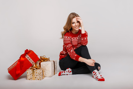 Funny beautiful young woman model in red fashion vintage sweater sits near gifts Stock Photo