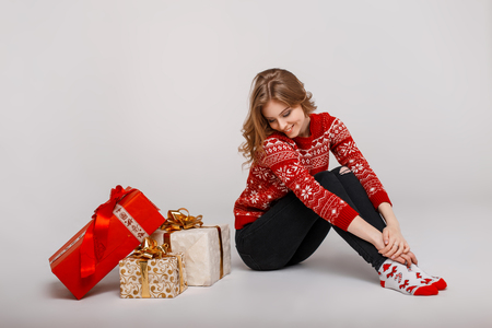 Young happy girl in vintage winter sweater sits near gifts