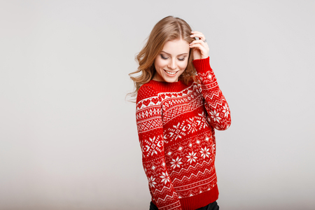 Happy beautiful model woman in red sweater with ornament