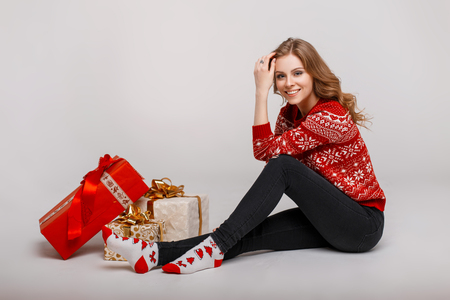 Cheerful beautiful young woman with a smile in a red Christmas sweater with socks sitting near a gift on a gray background Banco de Imagens