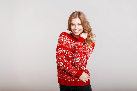 Happy beautiful young girl with cute smile in vintage red sweater on gray background Stockfoto