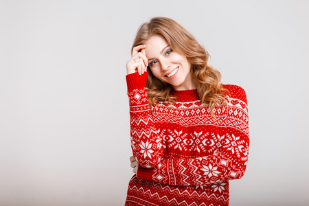 Beautiful happy young woman in a red trendy sweater on a gray background