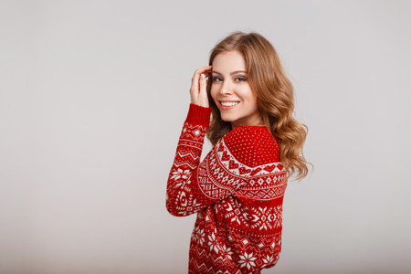 Happy young woman in a trendy fashion winter red sweater on a gray background