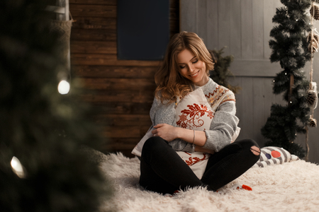 Beautiful young european model woman in a vintage winter sweater with a pillow sitting on the bed